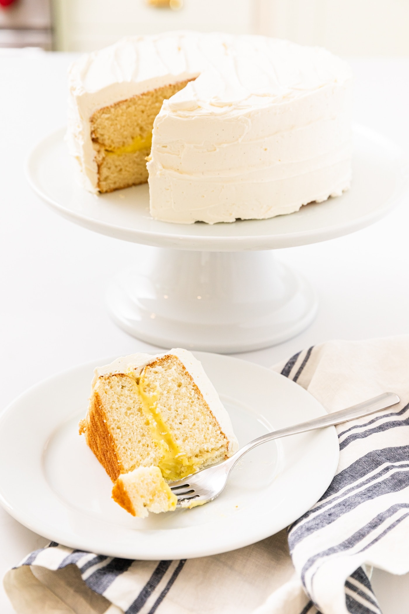 White frosted layer cake sitting on white cake stand in background with slice of cake sitting on white plate with fork in front all one white countertop
