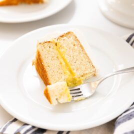 Slice of white cake with fork scooping off piece topped with white frosting and yellow colored middle layer sitting on white plate on white countertop