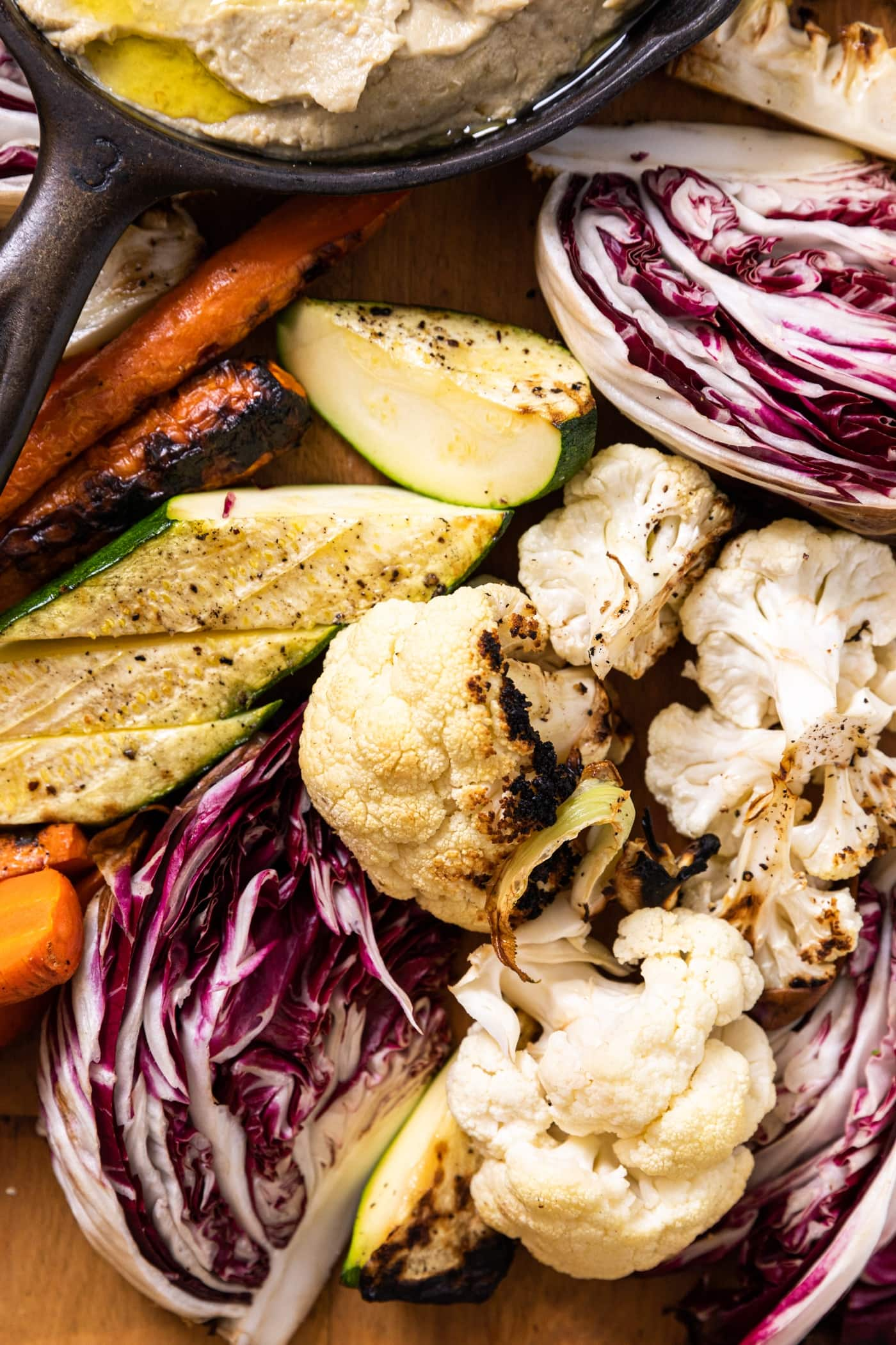 Assortment of grilled vegetables including zucchini, cauliflower, and carrots sitting on wood board