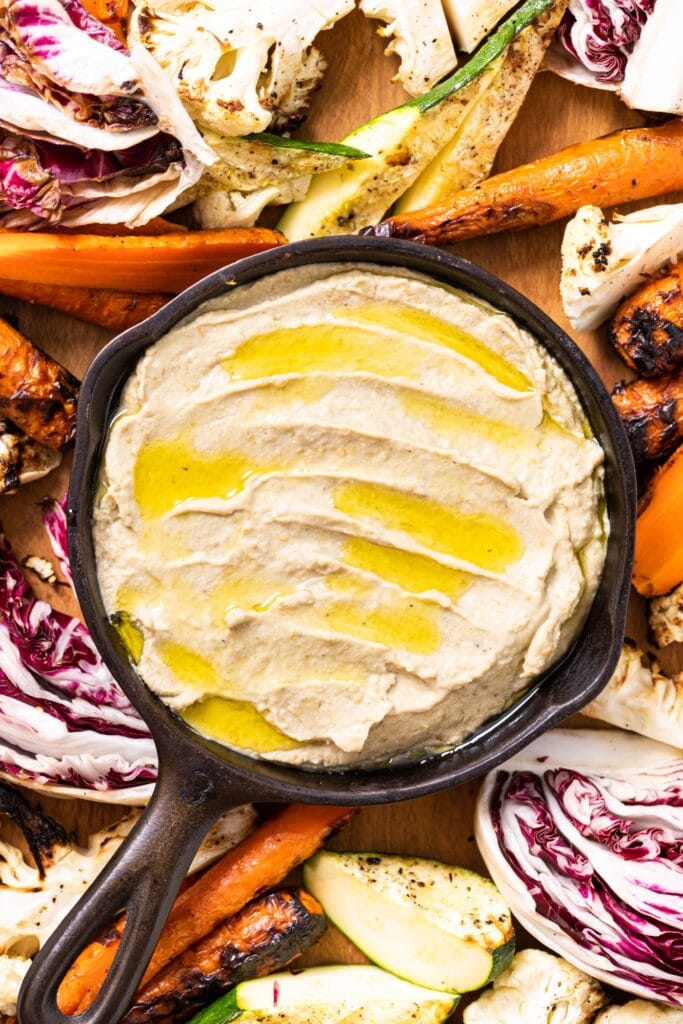Top down view of small cast iron skillet holding light brown colored Baba ganoush with drizzled olive oil over the top amongst grilled vegetables