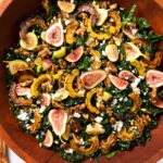 Top down view of hearty kale salad in wooden bowl topped with figs and squash and feta cheese on white countertop
