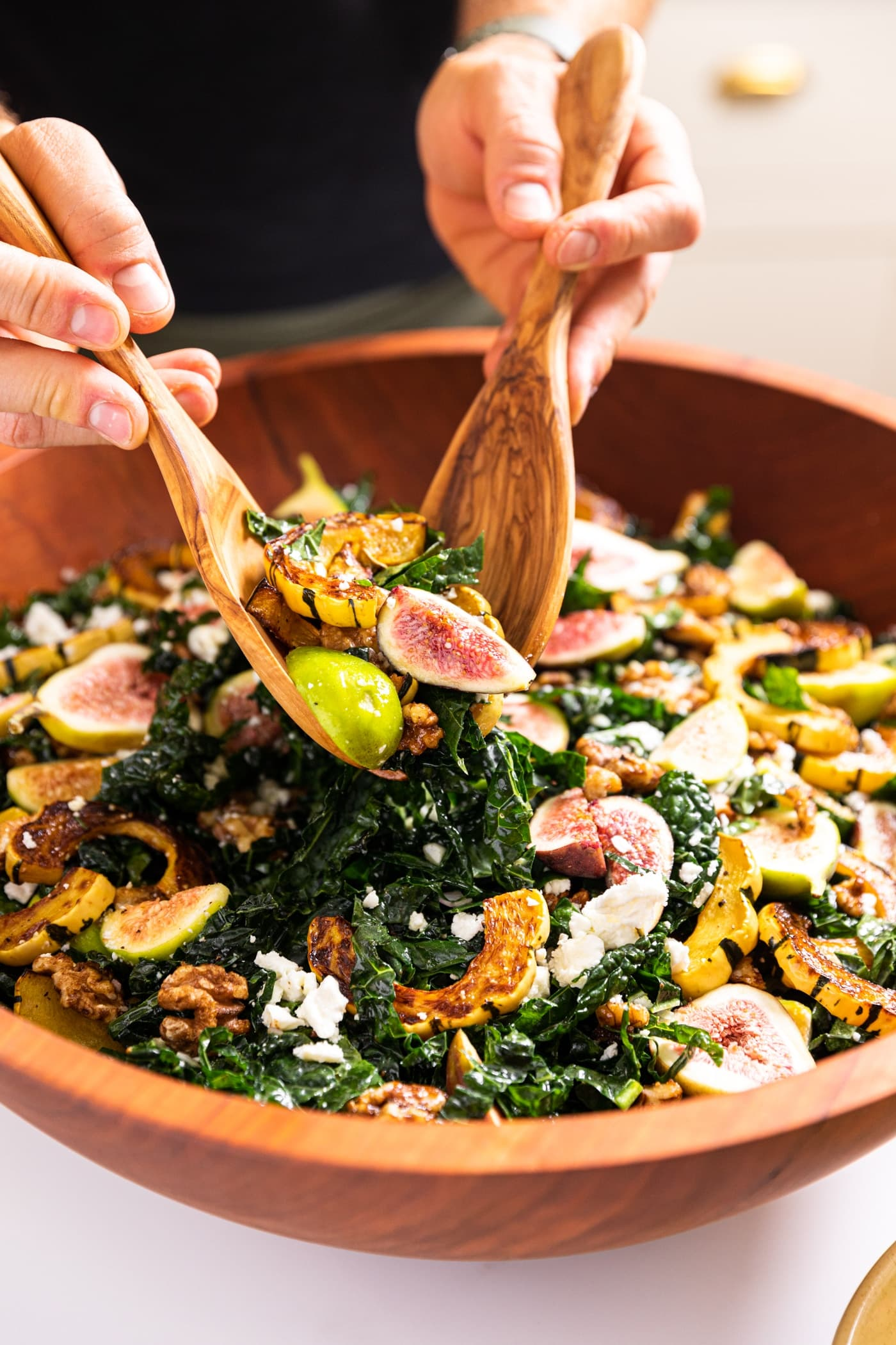 Two hands holding wooden tongs dipping salad out of a wooden bowl with pieces of kale and fig and squash
