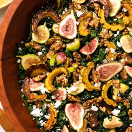 Top down view of large wooden bowl filled with kale salad topped with figs, squash, walnuts, and crumbled white feta