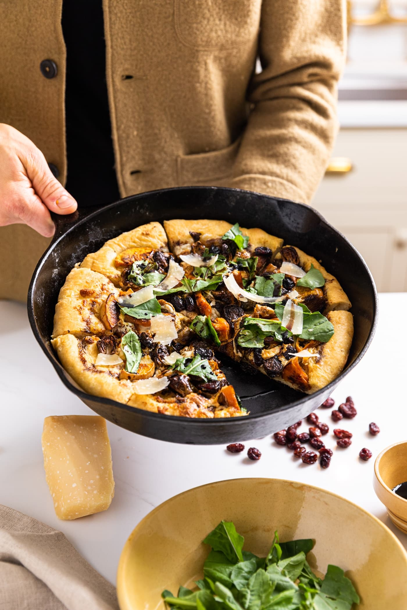 Two hands holding black cast iron skillet filled with rustic pizza topped with green pieces of arugula and cranberries