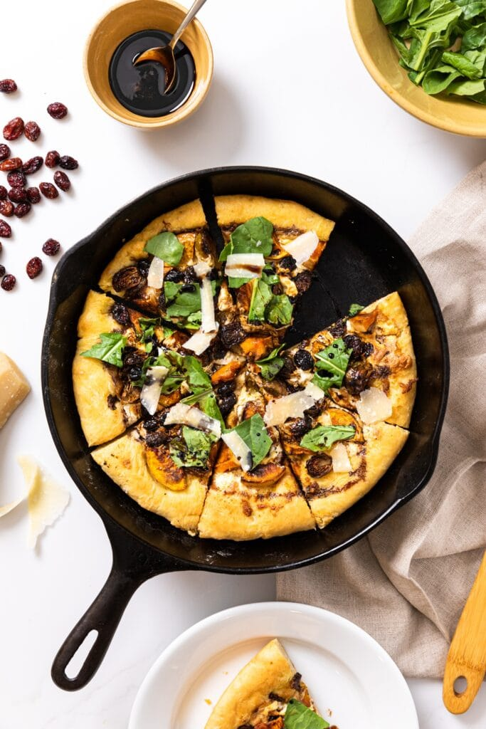 Top down view of rustic pizza sitting in cast iron skillet topped with arugula all on white countertop