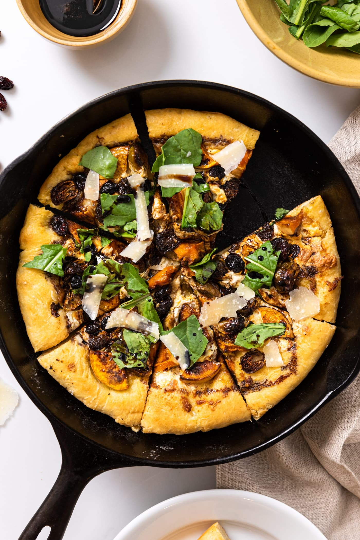 Top down view of black skillet with homemade pizza inside topped with arugula and sitting on a white countertop with other ingredients all around
