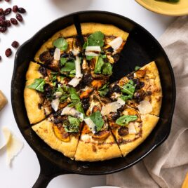 Top down view of black cast iron skillet sitting on white countertop with pizza in skillet topped with arugula