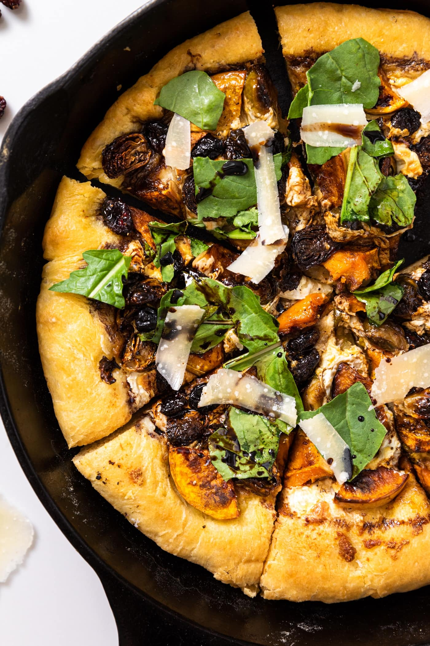 Top down view of cast iron skillet filled with rustic homemade fall pizza with butternut squash and Brussels sprouts on top