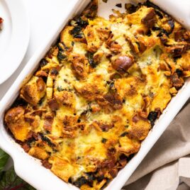 Top down view of white casserole dish filled with brown colored egg strata sitting on white countertop