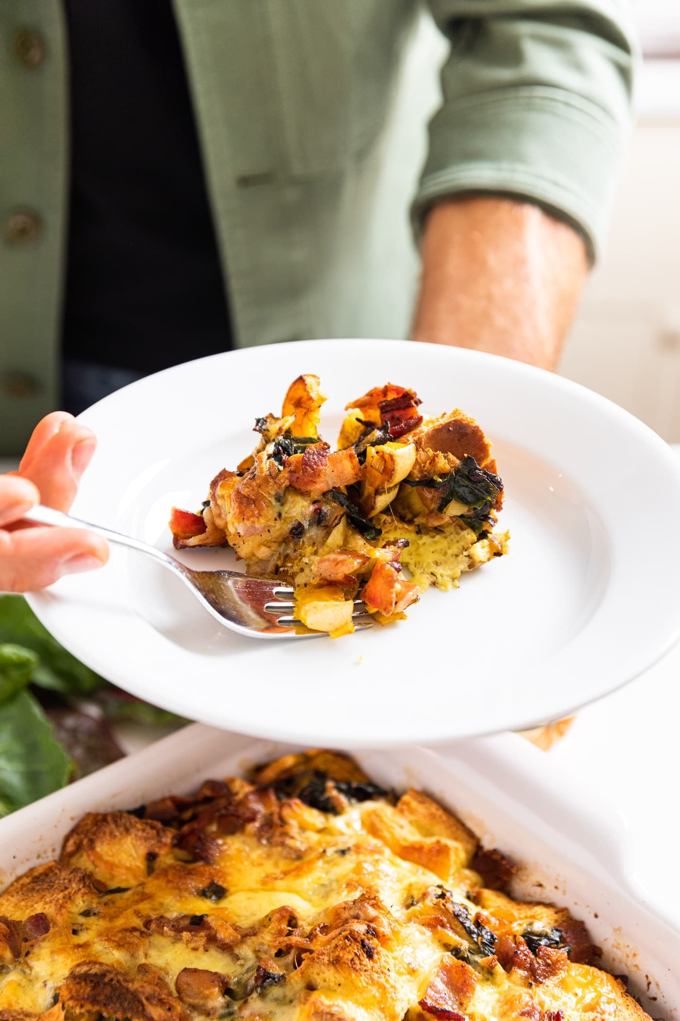 Hand holding white plate filled with scoop or squash strata with fork taking out a piece with rest of strata in white casserole dish below