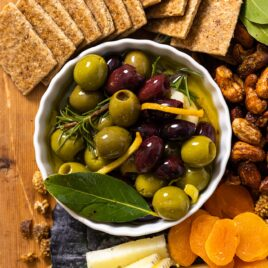 Top down view of small white bowl filled with black and green marinated olives sitting on wood board with cheese and crackers and dried fruit