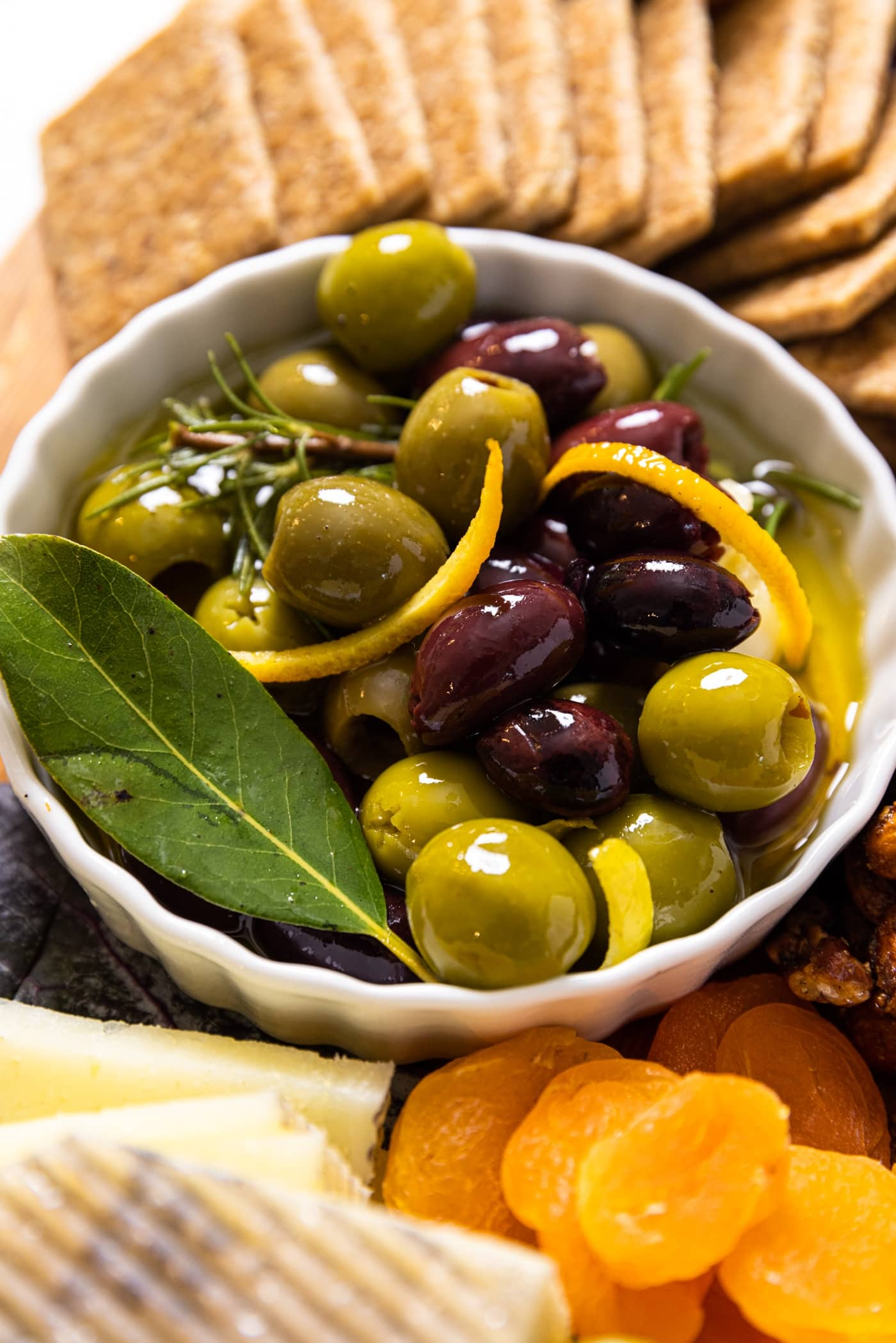 Small white bowl filled with marinated olives with slices of citrus zest sitting on wood board with crackers and dried apricots
