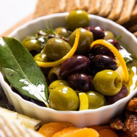 Small white bowl filled with green and black olives with slices of lemon zest with a bay leaf sitting on wood board