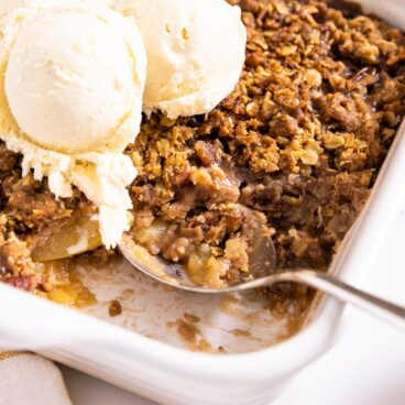 Large silver spoon sitting in white baking dish with a spoonful of apple crisp and three large scoops of ice cream on top
