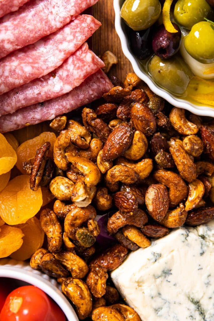 Top down view of spiced nut mixture sitting on wood board amongst olives, meats, dried fruit, and cheese