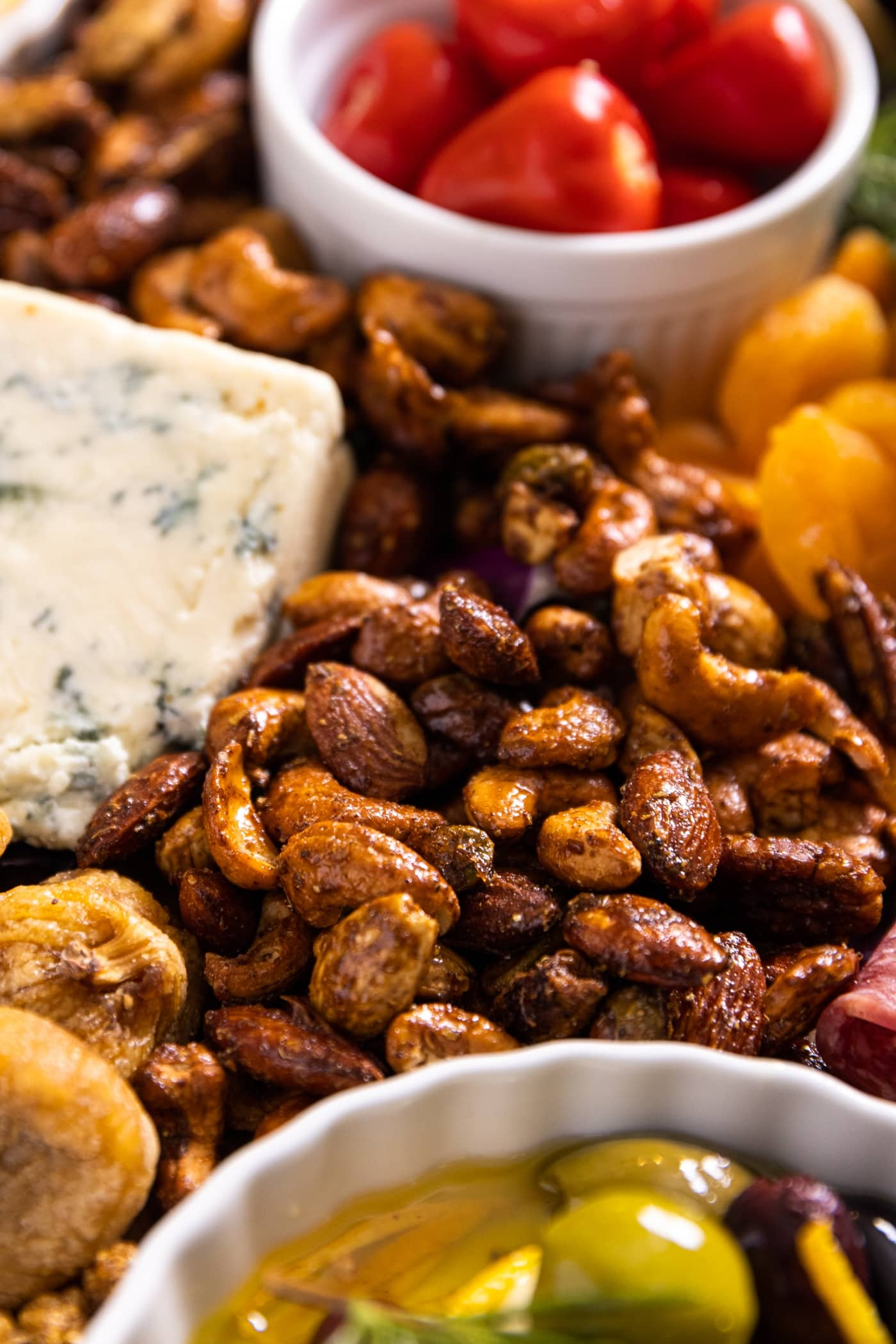 Close up view of spiced nut mix sitting on charcuterie board amongst red stuffed peppers, olives, dried fruit, and blue cheese