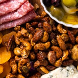 Top down view of a fall spiced nut mix sitting on wood board surrounded by dried fruits, cheese, and meats
