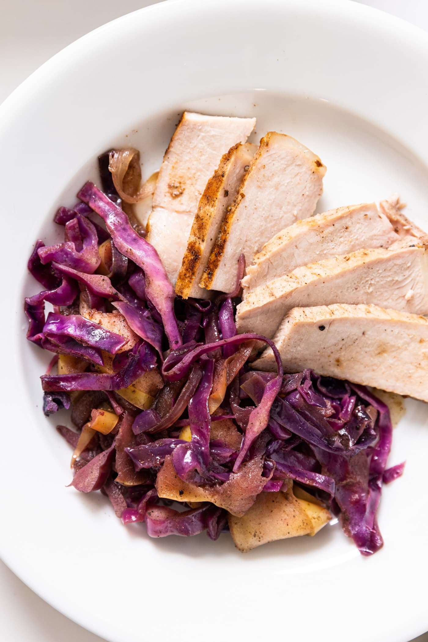 Top down view of white plate filled with slices of pork with red cabbage and apples on the side