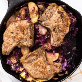 Top down view of black cast iron skillet sitting on white countertop with pork chops in the pan along with cabbage and apples