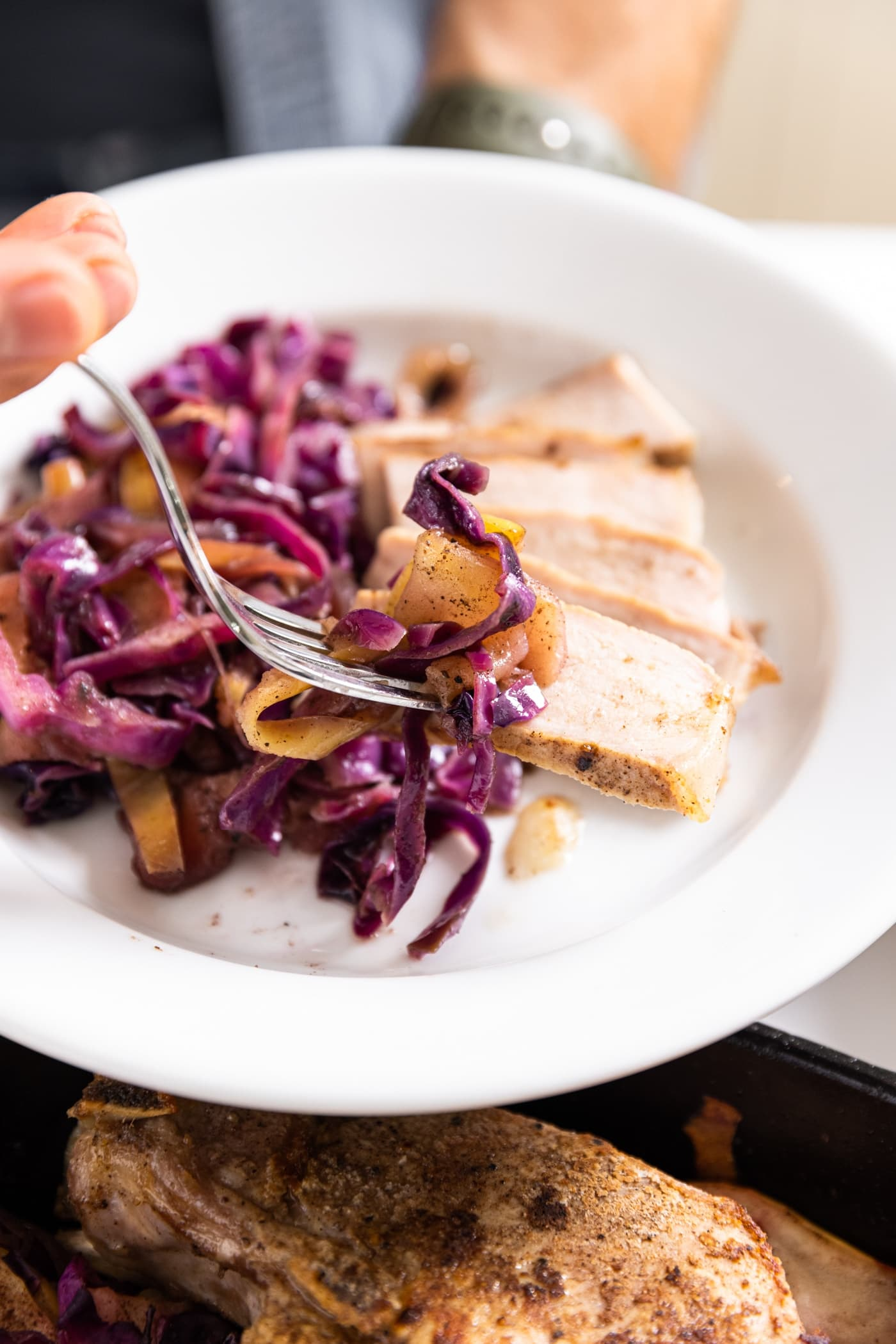 White plate filled slices of pork and a combination of red cabbage and apples with fork holding bite full