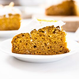 Large slice of pumpkin cake sitting on white plate with other slices of cake in background all on white countertop
