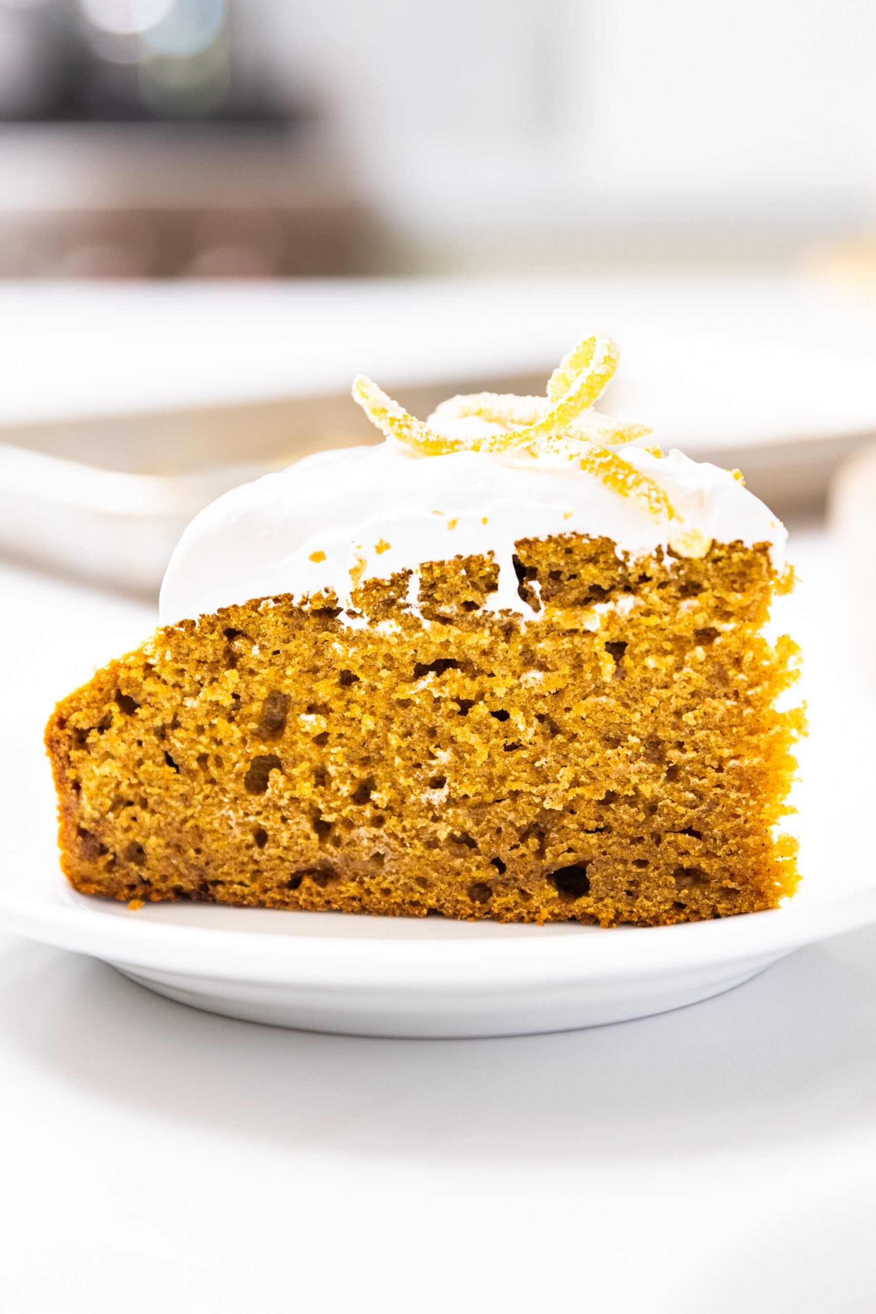 Close up side view of pumpkin applesauce cake topped with whipped topping and candied orange zest pieces