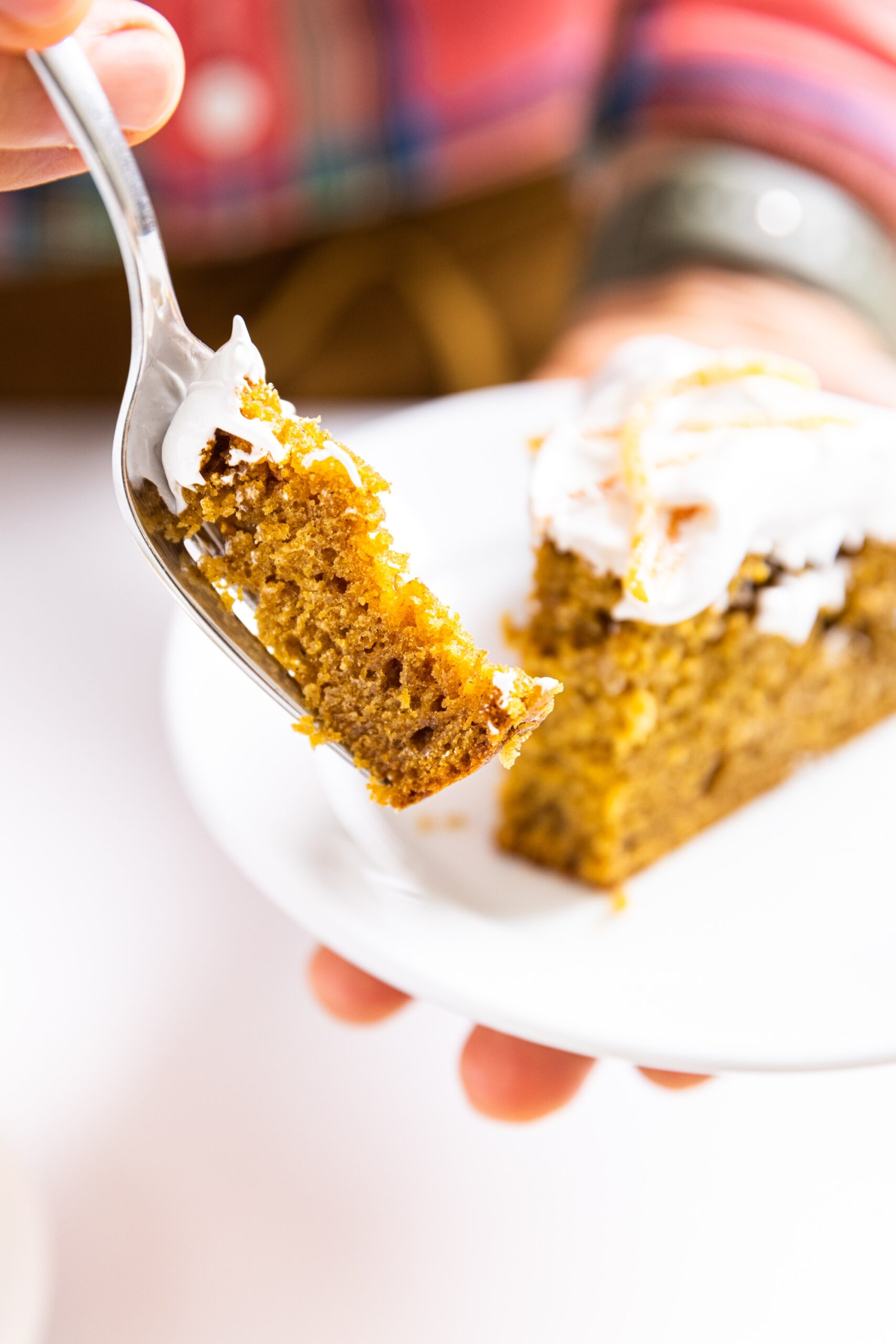 Hand holding fork bite of pumpkin applesauce cake with hand holding other part of cake