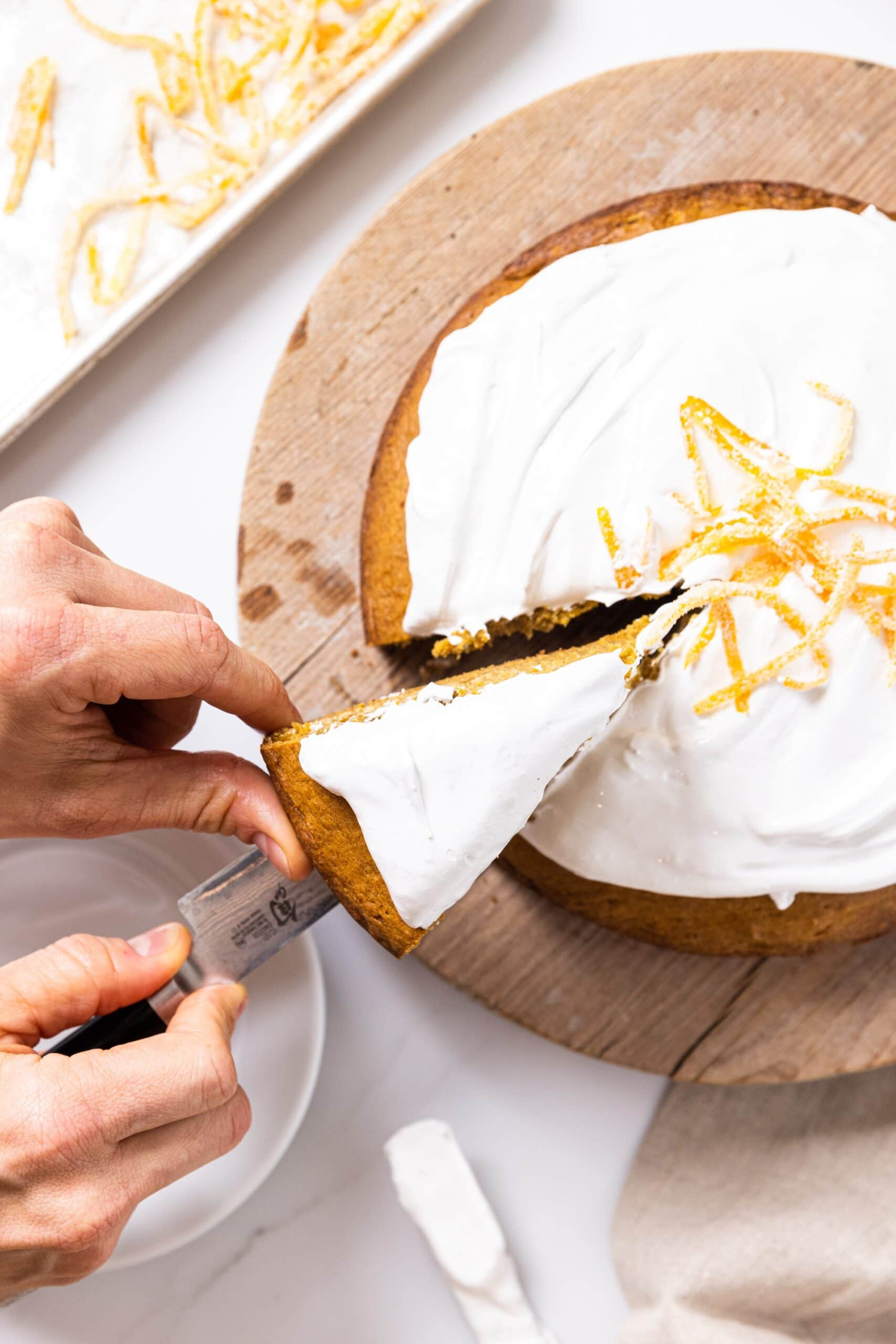 Top down view of hand taking slice of pumpkin cake with white whipped topping out of rest of cake