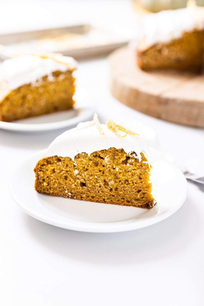 Slice of pumpkin cake sitting on white plate topped with white whipped cream with other slice and rest of cake in background