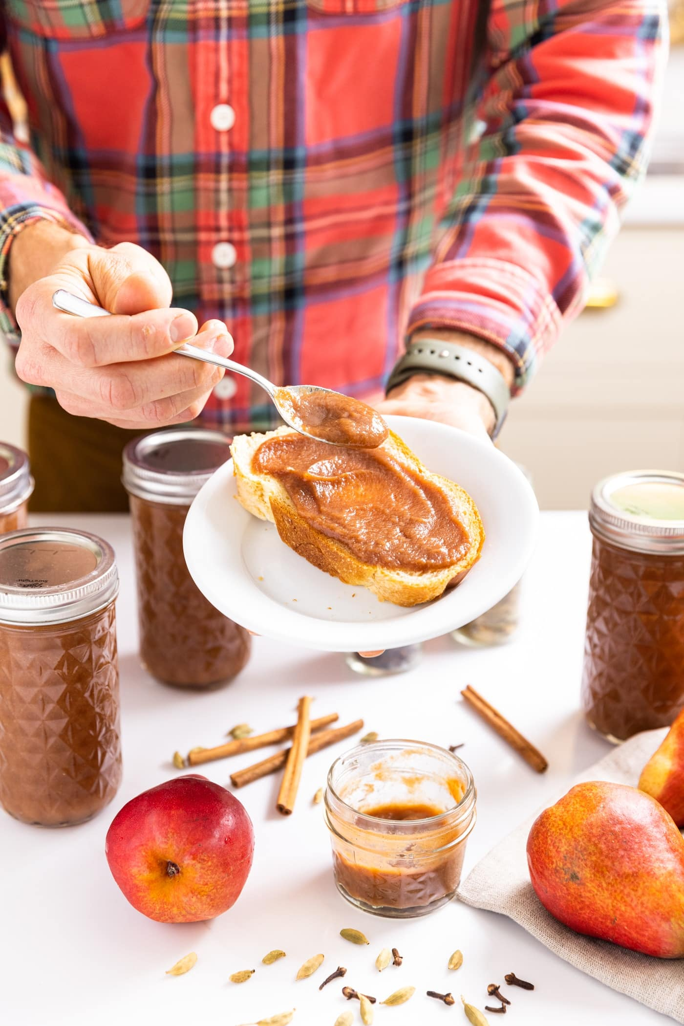 Two hands holding white plate with slice of bread on it with spoon spreading pear butter onto bread