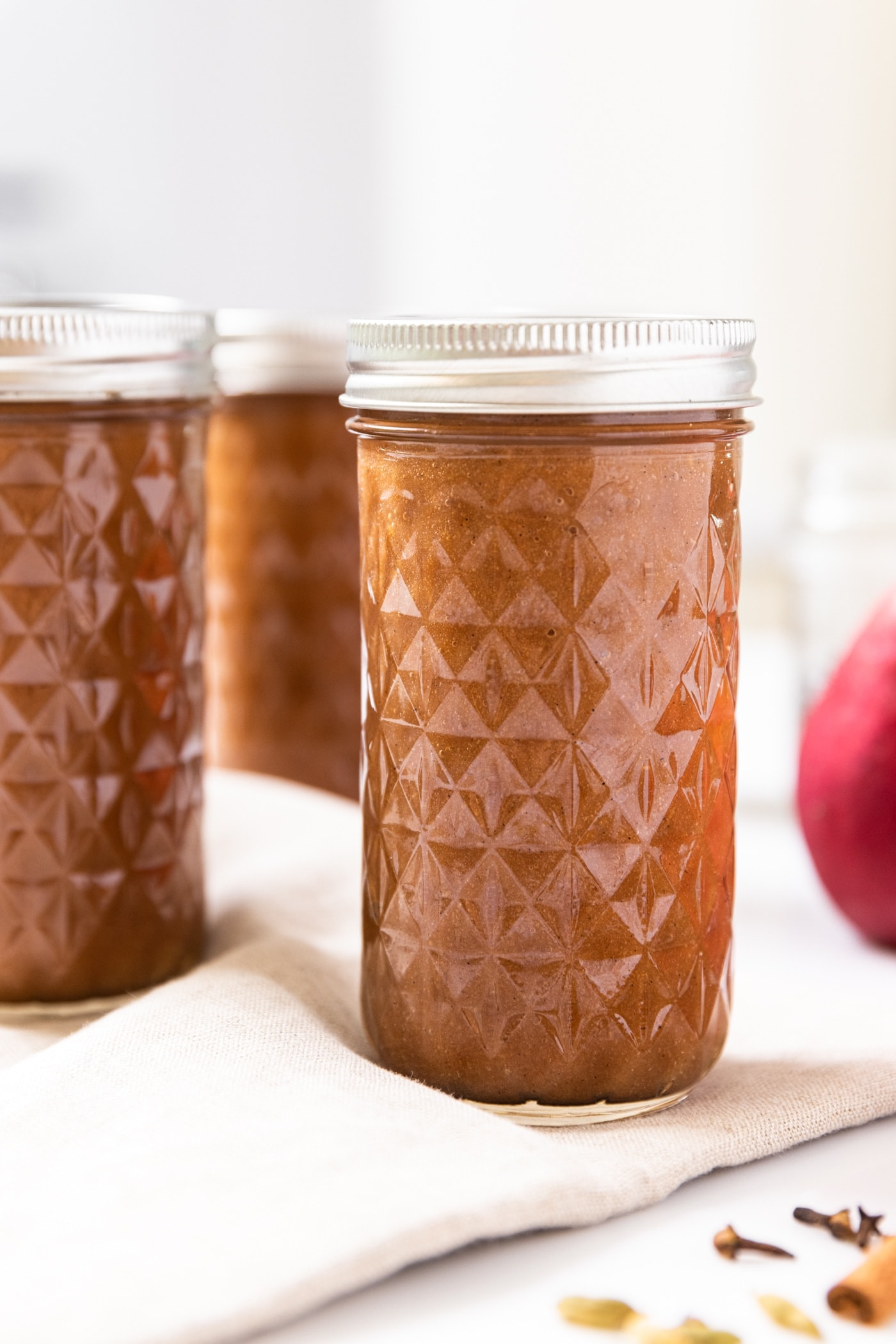 Narrow tall glass jar with diamond design filled with brown colored pear butter after being in the canner sitting on white countertop