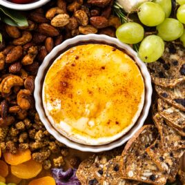 Top down view of small white bowl sitting on charcuterie board filled with baked Brie with yellow colored honey and chipotle on top
